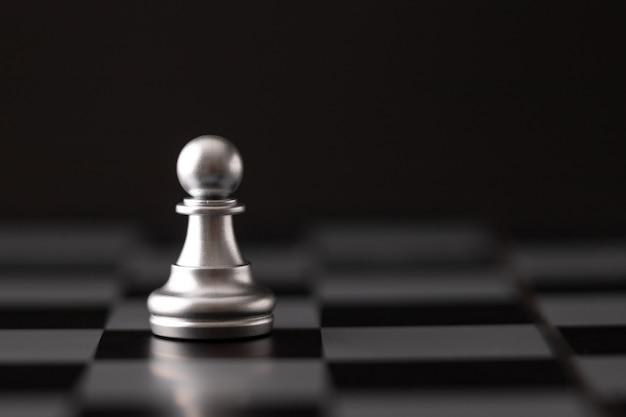 Zilveren chip op het schaakbord Premium Foto