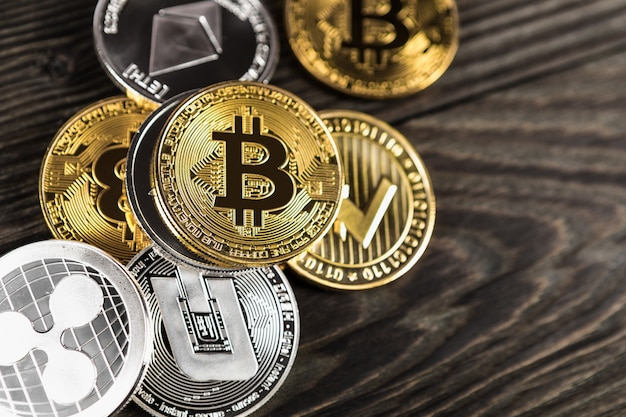 Zilveren en gouden munten met bitcoin, rimpel en etherische symbool op hout Premium Foto