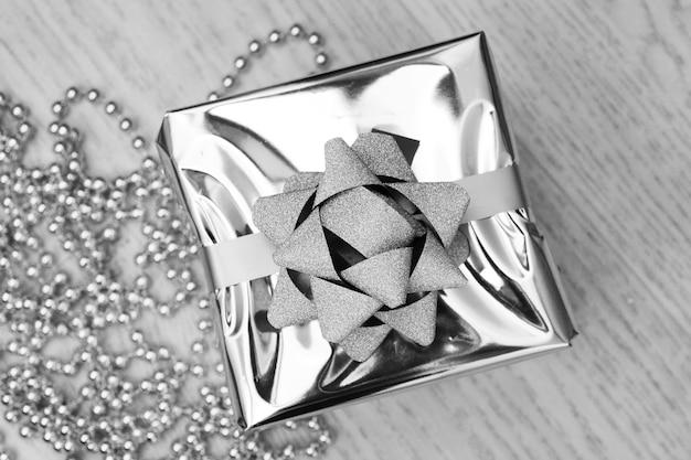 Zilveren geschenkdoos op een houten bovenaanzicht als achtergrond. kerst vakantie concept. plat leggen. Premium Foto