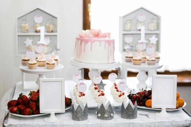 Zilveren kronen staan op de tafel met roze bakeru en bessen Gratis Foto