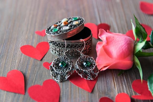 Zilveren oorbellen met bloem en rode papieren harten. Premium Foto