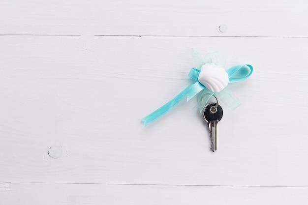 Zilveren sleutels met blauw lint en zeeschelp Premium Foto