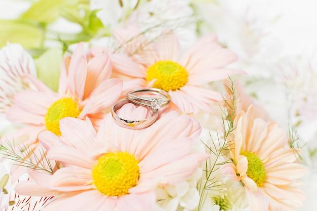 Zilveren trouwringen op roze gerberabloemen Gratis Foto