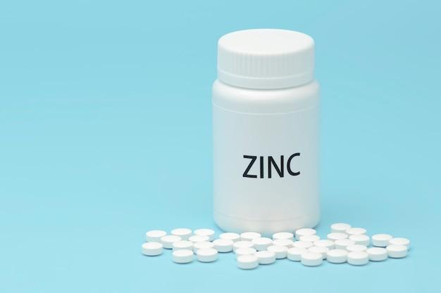 Zink in witte flesverpakking met verspreide pillen. Premium Foto