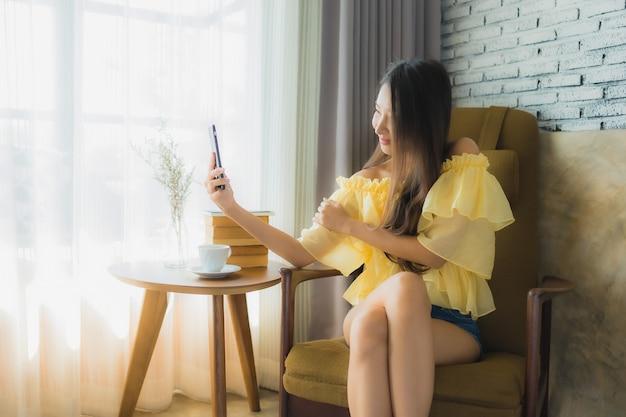 Zit de portret jonge aziatische vrouw die mobiele telefoon met koffiekop en gelezen boek met behulp van op stoel in woonkamer Gratis Foto