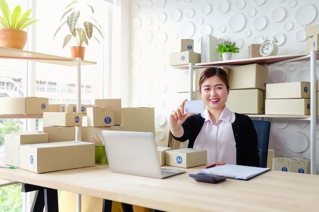 Zitten de levensstijl bedrijfsvrouwen die in bureau zitten witte kaartglimlach die, mkb-kleine onderneming werken Premium Foto