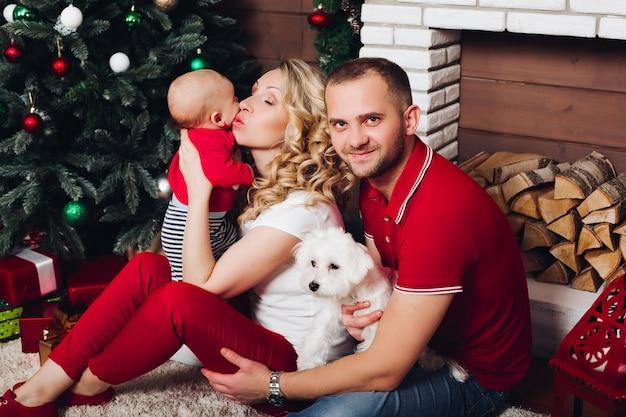 Zittend in de buurt van open haard met zoontje en schattige hond en glimlachen Premium Foto