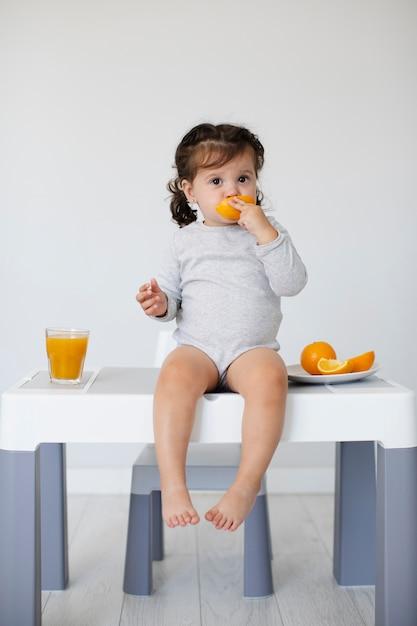 Zittend op de tafel baby meisje oranje eten Gratis Foto