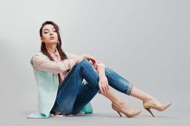 Zittend portret jong donkerbruin meisje die in roze blouse, turkoois jasje, gescheurde jeans en roomschoenen op grijze achtergrond dragen Premium Foto