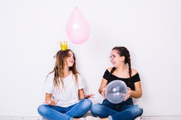 Zittend tieners spelen met ballonnen Gratis Foto