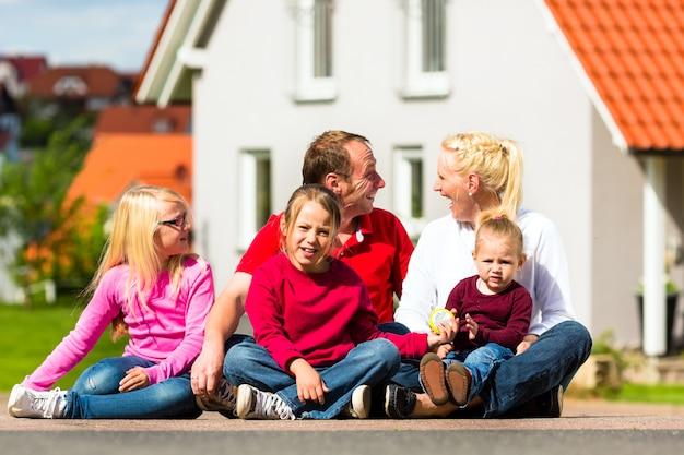 Zittend voor huis en gelukkige familie Premium Foto