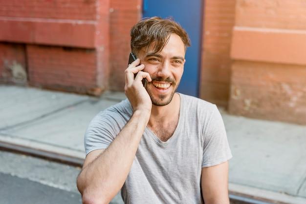 Zittende man praten over de telefoon Gratis Foto