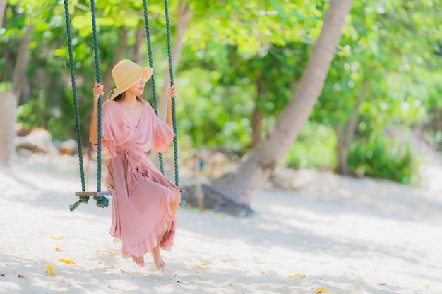 Zitting van de portret de jonge aziatische vrouw op schommelingskabel en overzees rond strand overzeese oceaankokosnotenpalm Gratis Foto