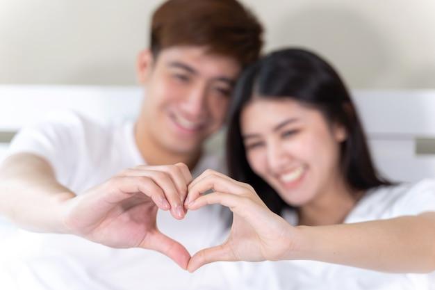 Zitting van het portret maakt de gelukkige jonge paar en het glimlachen op bed en hand samen hartvorm Gratis Foto