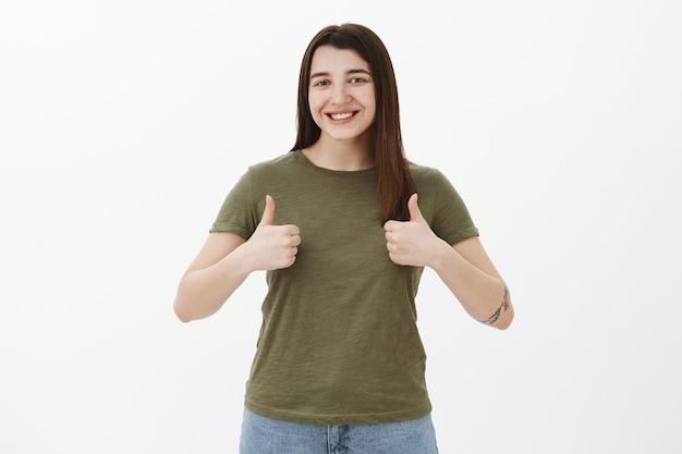 Zo geweldig, net als jouw idee. portret van vrolijk en blij schattig 20s meisje met tatoeage glimlachend opgetogen en vrolijk duimen opdagen ter goedkeuring en ondersteuning gebaar, reageren op uitstekende suggestie Gratis Foto