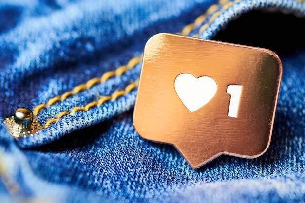 Zoals hartsymbool. zoals tekenknop, symbool met hart en één cijfer. social media netwerkmarketing. blue jeans textuur achtergrond. Premium Foto