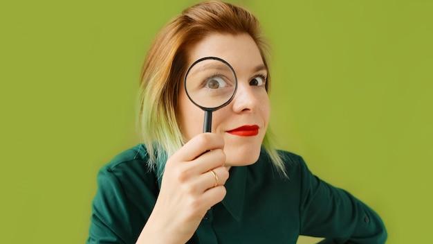 Zoeken. een jonge vrouw met een vergrootglas zoekt, onderzoekt en bestudeert. Premium Foto