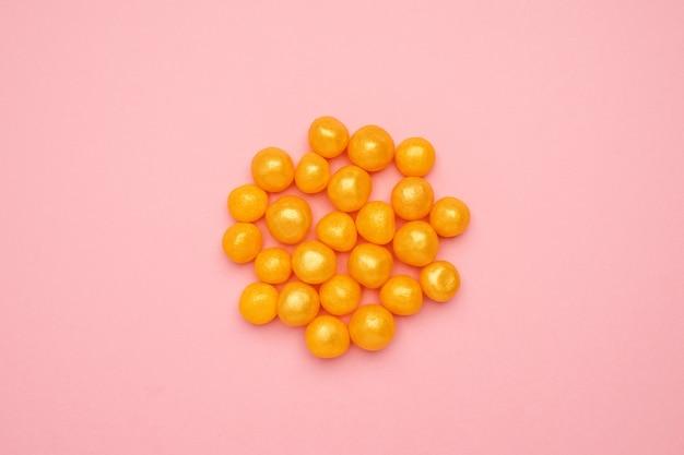 Zoet geel suikergoed op een roze, rond zoet voedsel Premium Foto