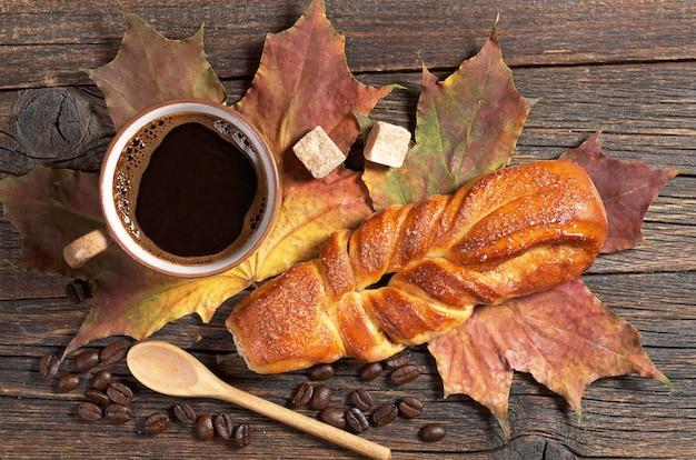 Zoet gevlochten broodje en kop warme koffie Premium Foto