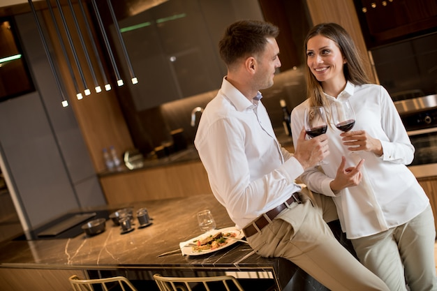Zoet paar die rode wijn na een romantisch diner hebben drinken bij luxekeuken Premium Foto