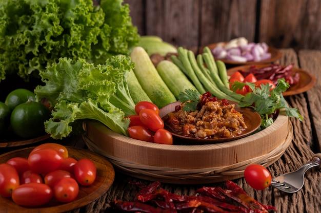 Zoet varkensvlees in een houten kom met komkommer, kouseband, tomaten en bijgerechten. Gratis Foto