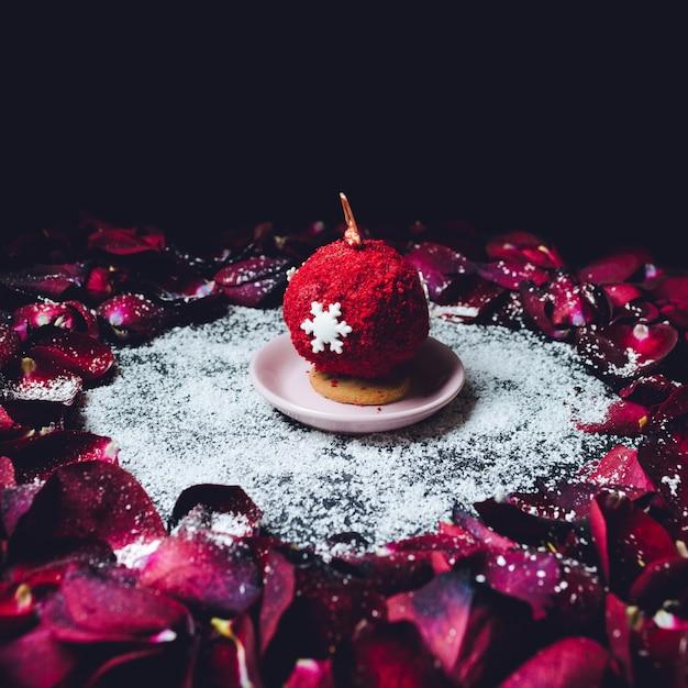 Zoete bal bedekt met rode poeder stands in de cirkel van rode rozenblaadjes Gratis Foto