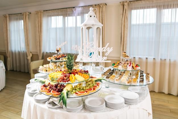 Zoete bruiloft buffet met verschillende desserts en fruit Premium Foto