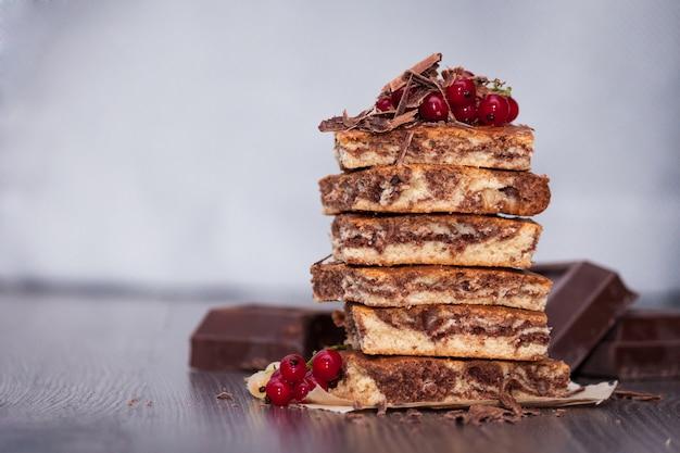 Zoete cake met cacaopoeder zebra met bessen en chocolade op donkere houten achtergrond. kopieer ruimte Premium Foto