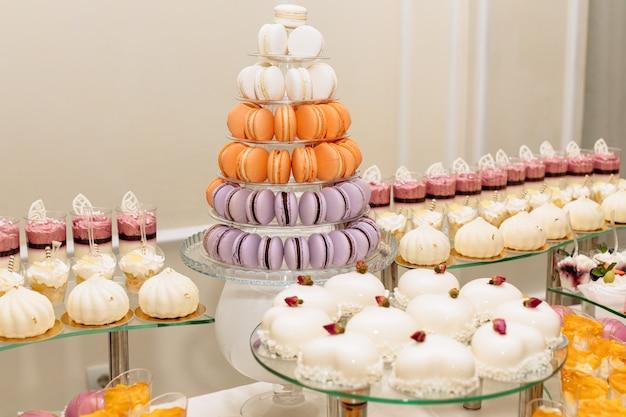 Zoete desserttafel of candybar. tafel met verschillende snoepjes voor feest. vakantiebuffet met cupcakes en andere desserts. macaron, cupcakes, marshmallow close-up Premium Foto