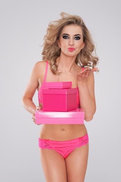 Zoete en sexy vrouw in lingerie roze geschenken geven Gratis Foto
