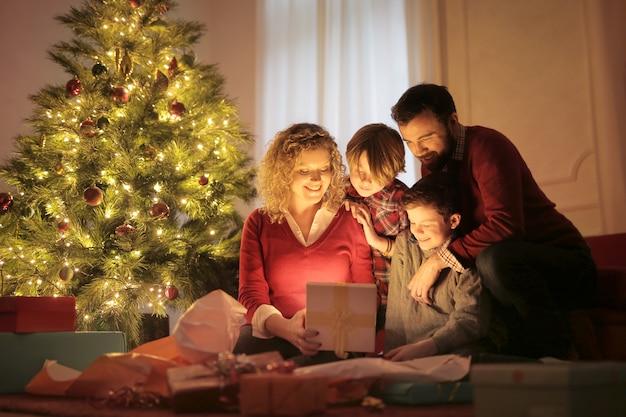 Zoete familie die kerstmisgiften in de avond opent Premium Foto
