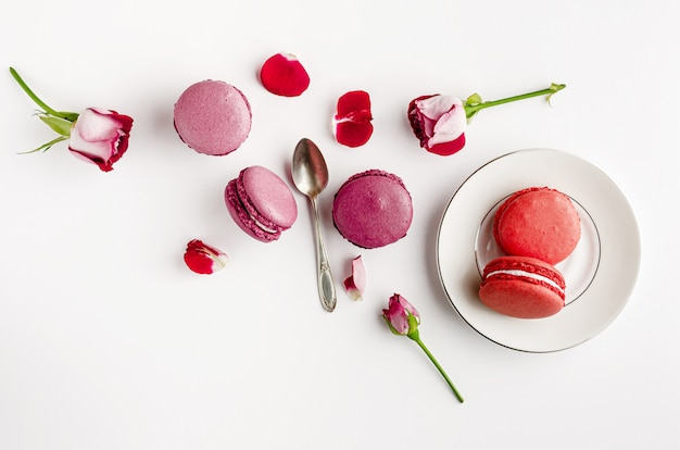 Zoete franse dessert en rozen op witte achtergrond Premium Foto