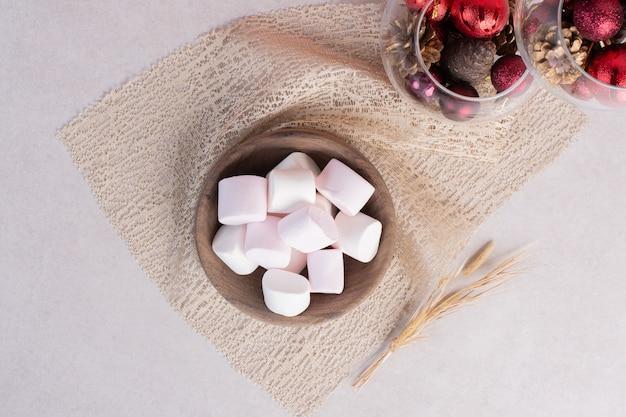Zoete marshmallows op een houten bord op jute Gratis Foto