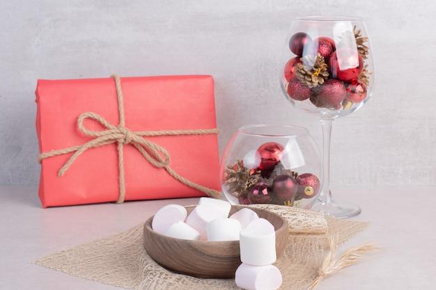 Zoete marshmallows op houten plaat met glas rode kerstballen Gratis Foto