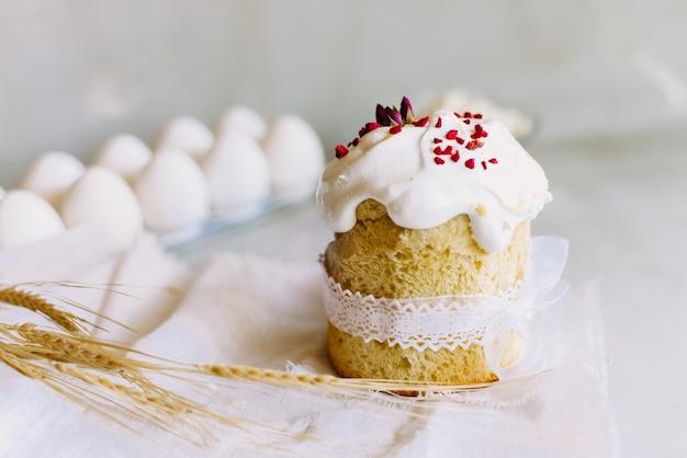 Zoete pasen-cake op een lichtgrijze achtergrond naast de aartjes van rogge. het concept van een heldere vakantie Premium Foto