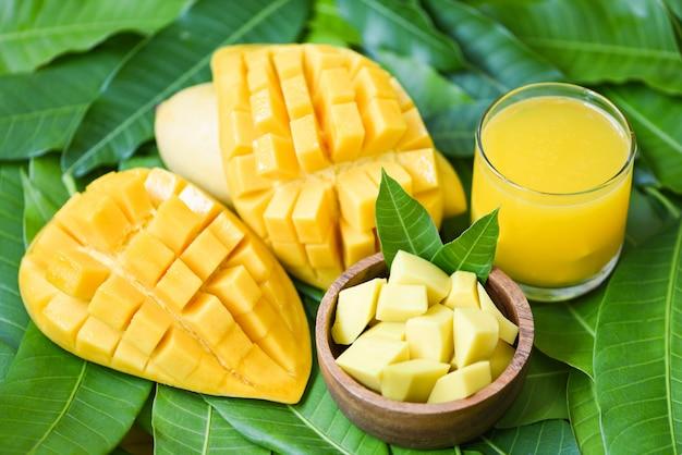 Zoete rijpe mango's - mangosapglas met mangoplak op mangobladeren van het fruitconcept van de boom tropisch zomer Premium Foto