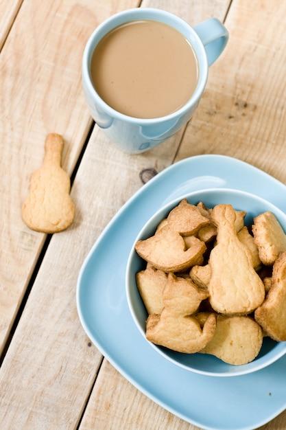 Zoete smakelijke koekjes in de blauwe plaat, een kopje koffie met melk en notebook op houten ongeverfde tafel. Premium Foto