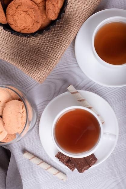 Zoete snacks, kopje thee op lichte achtergrond Gratis Foto