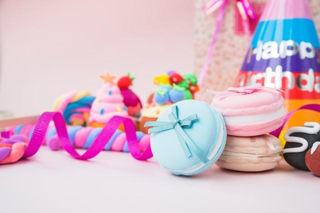 Zoete snoepjes; bitterkoekjes; linten en verjaardag hoed op roze achtergrond Gratis Foto
