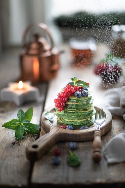 Zoete spinazie pannenkoeken met krenten en bosbessen en honing. Premium Foto