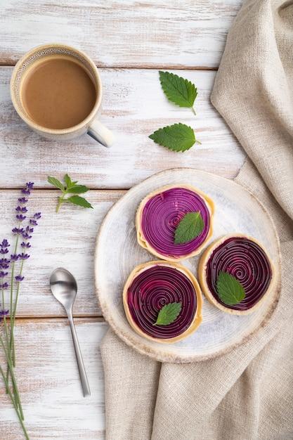Zoete taartjes met gelei en melkroom met kopje koffie Premium Foto