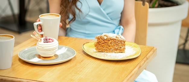 Zoete verschillende stukjes cake op de borden aan de tafel op de achtergrond van een vrouw met een kopje koffie in een café Premium Foto