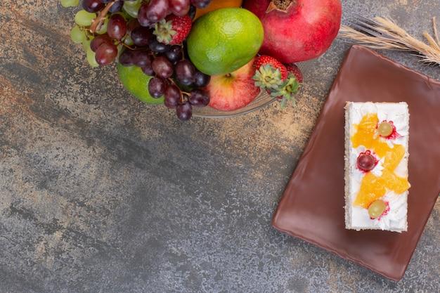 Zoete verschillende vruchten op glasplaat met fluitje van een cent op donkere plaat Gratis Foto