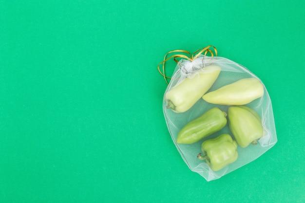 Zoete verse paprika in eco natuurlijke zakken naaien van mesh doek op groene achtergrond met kopie ruimte. zero waste food shopping concept. uitzicht van boven. Premium Foto