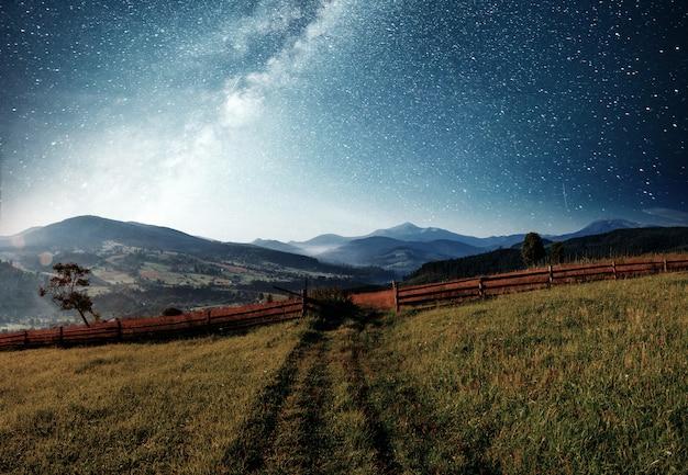 Zomer berglandschap. hoog gras en levendige nachtelijke hemel met sterren en nevel en galaxy. diepe lucht astrofoto Premium Foto