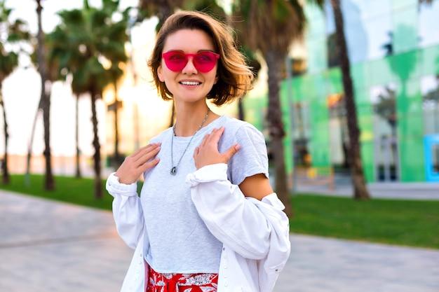 Zomer buiten mode heldere portret van stijlvolle trendy lachende vrouw hipster stijlvolle outfit, wit denim jasje en neon zonnebril, palmen rond, gelukkig reizen stemming. Gratis Foto