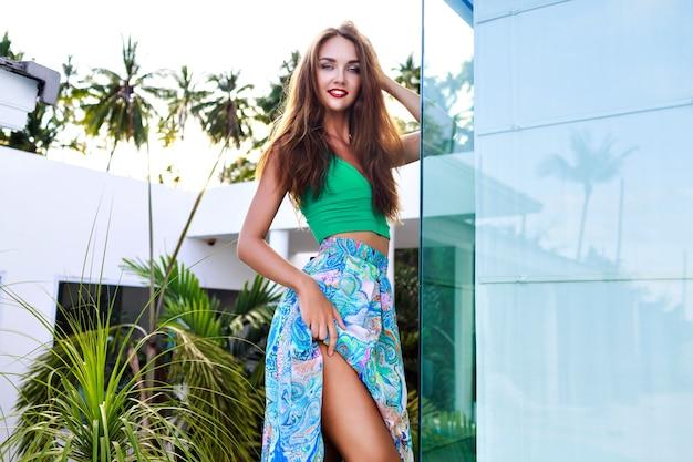 Zomer buiten mode portret van prachtige brunette vrouw met lange haren en lichte make-up, sexy zijden jurk dragen, poseren in luxevilla, avondzonlicht Gratis Foto