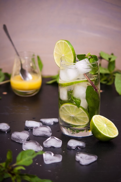 Zomer coctail mojito met ijs, munt, limoen op een grijze achtergrond. kopieer ruimte. Premium Foto