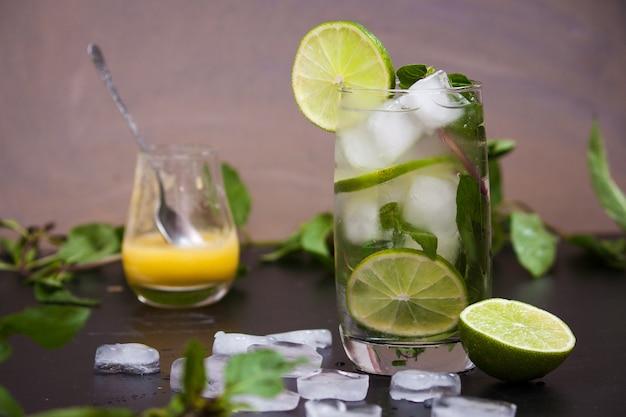 Zomer coctail mojito met ijs, munt, limoen op een grijze achtergrond. Premium Foto
