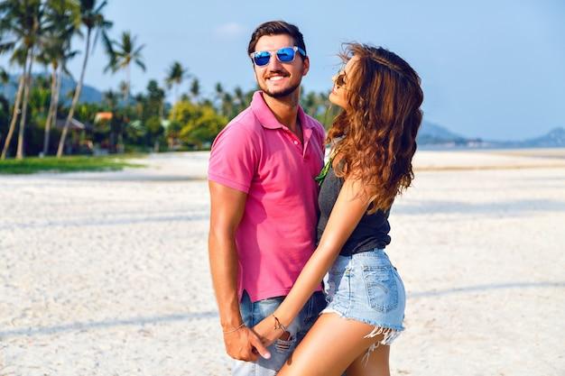Zomer heldere mode portret van mooie verliefde paar, stijlvolle lichte casual hipster kleding en zonnebril dragen, hand in hand knuffels en genieten van hun vakantie in de buurt van de oceaan. Gratis Foto